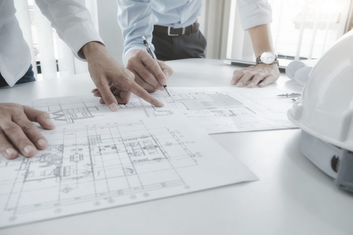 Image of engineer meeting for architectural project. working with partner and engineering tools on workplace vintage tone.
