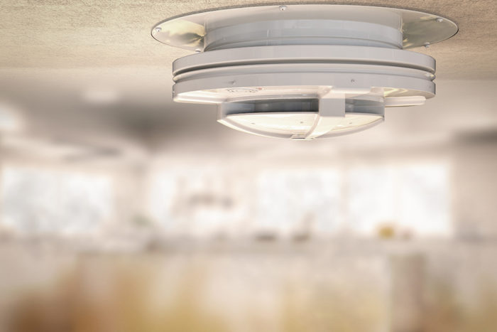 3d rendering smoke detector on ceiling with smoke in kitchen